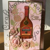 A4 size 80th Birthday card for a special Mum. Made using custom made bottle die, Tattered Lace Lavish Blooms Poppy and Majestic Rose dies, Quickutz Cookie cutter number dies & Britannia sentiment dies, plus various labels & circle dies and embossing folder for bottle seal and labels - craftybabscreativecrafts.co.uk