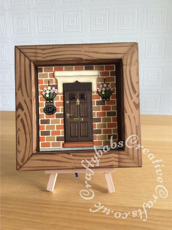 New Home Shadow Box card made using a variety of dies including Marianne bricks die (comes with embossing folder), XCut georgian door die set (cut into for over door stone and step), Spellbinders nesting ovals die for name plaque, bird cage die snipped for hanging baskets. Nesting rectangles die for door scored on score board to create moulded door panels, Tattered lace small flowers die. Glossy accent used on windows in door and house name plaque. Frame made using template created from a box that Christmas cards came in, inked with distress inks through a wood grain stencil. Frame stand cut using Sizzix Bigz Tim Holtz small easel die - craftybabscreativecrafts.co.uk