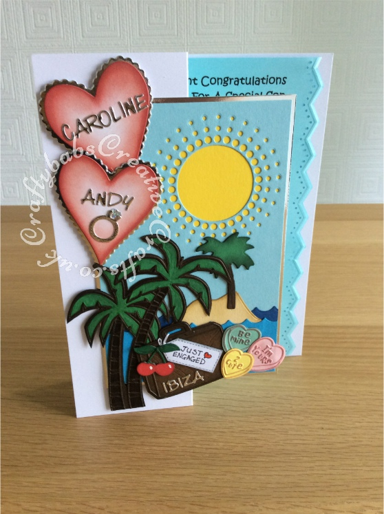 Individualised Engagement card made using a variety of dies including; Cuttlebug Disney dies/embossing folders; love always, bon voyage and palm tree set (can't remember name), Sizzix framelits nesting plain and scallopped hearts dies, Memory box small circle burst die, Sizzix thinlits cherries die from rock and roll sundae set, Quickutz 2x2 single cutz engagement ring die, X cuts build a scene 'Ship Ahoy' pirate ship set for sea, island & small palm trees. Die-versions Marker micro font die for letters - craftybabscreativecrafts.co.uk