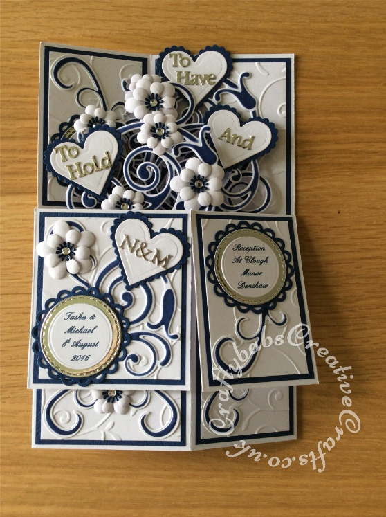 Pop up Wedding card made using a number of dies including; Spellbinders nesting plain and scalloped hearts dies, Cheery lynn flowers dies, Anna griffin flourish scroll die, spellbinders lacey circles dies, Crea Nest lies no 33 dies, leabilities frame square curve die set (for small flourishes). Joy cut & emboss wedding die set, Background embossed with Xcut A4 folder. Die cuts inked whilst in die in matching distress ink (Chipped Sapphire) - craftybabscreativecrafts.co.uk