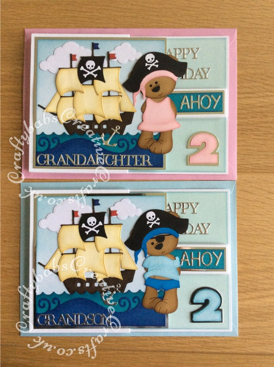 Pirate double Z fold birthday cards made for twins having a pirate themed birthday party. Made using a variety of dies including Custom made wooden Tattoo bear die, Go Kreate Boo Bear Pirate outfit, summertime outfit and dress dies, Xcut build a scene nautical dies, Tattered Lace sentiment dies, Apple Blossom capitals alphabet die and Sizzix originals shadow box numbers dies. - craftybabscreativecrafts.co.uk