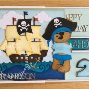 Pirate double Z fold birthday cards made for twins having a pirate themed birthday party. Made using a variety of dies including Custom made wooden Tattoo bear die, Go Kreate Boo Bear Pirate outfit, summertime outfit and dress dies, Xcut build a scene nautical dies, Tattered Lace sentiment dies, Apple Blossom capitals alphabet die and Sizzix originals shadow box numbers dies - craftybabscreativecrafts.co.uk