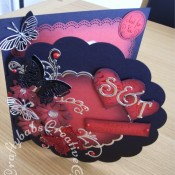 8″ square Ruby Wedding Anniversary card made using various dies including; Quickutz lifestyle scalloped circle dies, Sizzix originals hearts die, Xcut Petal posies dies, Cheery Lynn exotic butterfly die and Memory Box Kaleidoscope and Moonlight butterfly dies and Marianne frame and swirls set flourish dies. - craftybabscreativecrafts.co.uk