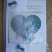Feathers & Orchids Wedding card. Orchids hand cut and embossed in parchment, Dies used include Sizzix originals Hearts dies, Cuttlebug divine swirl embossing folder and Sizzix sizzlits wedding rings die. - craftybabscreativecrafts.co.uk