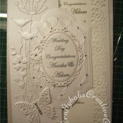 White on White Wedding card made using Couture creations tied together embossing folder, Spellbinders Papillons dies, Spellbinders small floral ovals die, Spellbinders labels 28 dies, Memory Box Prim Poppy die, Memory Box Tall Chloe stem dies and memory Box honeyblossom twig die - craftybabscreativecrafts.co.uk