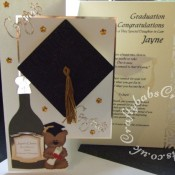 A4 Graduation Card with Pop up front, made using a variety of dies including Custom made wooden champagne bottle die, Go Kreate Boo Bear die, Custom made graduation die, Spellbinders labels 2 dies, Cuttlebug 'Congratulations embossing folder and sentiment die from Cuttlebug cut & emboss everyday greetings set. - craftybabscreativecrafts.co.uk