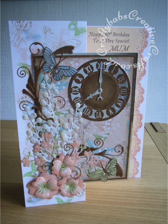 A4 Floral time themed 80th Birthday card made using a variety of dies including; Memory Box Gwyneth flourish die, Memory Box Kaleidoscope and Moonlight butterfly dies, Marianne Craftables Clock CR1234 dies, Cheery lynn Build a flower #1 set for stamens and Quickutz Wildflower die set for large flowers and floral sprays. - craftybabscreativecrafts.co.uk