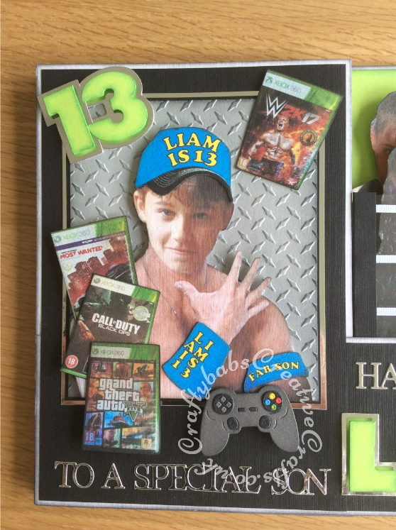 XL A4 WWE Double Z card with 3D pop up section made using photographs of the recipient and his actual computer games and CraftArtist Professional2 software to make him look like his favourite wrestlers. Dies used include Sizzix Originals Shadow Box alphabet and number dies, Sentiments from various Tattered Lace 3Die-mensions sets, Game controller die from Yvonne Creations and Diamond metal plate embossing folder by Hot Off The Press Paper Artist. 3mm gross grain ribbon and acetate used to create the wrestling ring - craftybabscreativecrafts.co.uk