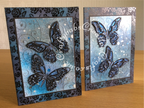 Inky Butterfly cards made using Xcut A4 delicate flourishes embossing folder and Sizzix Tim Holtz Detailed Butterflies thinlits dies. Card bases are pre printed forever friends card blanks that have been inked to co-ordinate. Background distress inked, sprayed and splattered with various pearlescent inks and Spectrum Noir Sparkle pen (clear). - craftybabscreativecrafts.co.uk