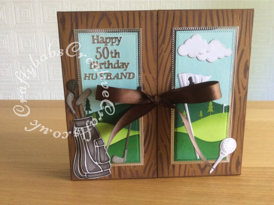 Golf themed Shadow Box Window Card made using a number of dies including; Tonic shadow Box Creations Die set 1635E, Tattered Lace sentiments dies, Lea'bilities Golf Bag & Clubs dies, Spellbinders golf die for flag and gold ball, Memory Box Dies, Mini Golf Carts, Memory Box Golf cart, Memory Box Golf landscape die, Clouds from Xcut Build a scene All aboard die set, Grass border from Xcut English Countryside Borders die set and Tattered Lace Panorama Trees (D634), The base card is plain brown which I have inked with distress inks in various shades of brown through a wood grain effect stencil. - craftybabscreativecrafts.co.uk