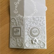 Pop up Silver Wedding Anniversary card made using a number of dies including; Spellbinders nesting plain and scalloped hearts dies, Cheery lynn flowers dies, Anna griffin flourish scroll die, spellbinders lacey circles dies, Crea Nest lies no 33 dies, leabilities frame square curve die set (for small flourishes). Joy cut & emboss wedding die set, Nellies nesting stitched squares dies, Background embossed with distress ink applied to folder using embossaliscious a4 folder. die cuts inked whilst in die in matching distress ink (Hickory Smoke). - craftybabscreativecrafts.co.uk