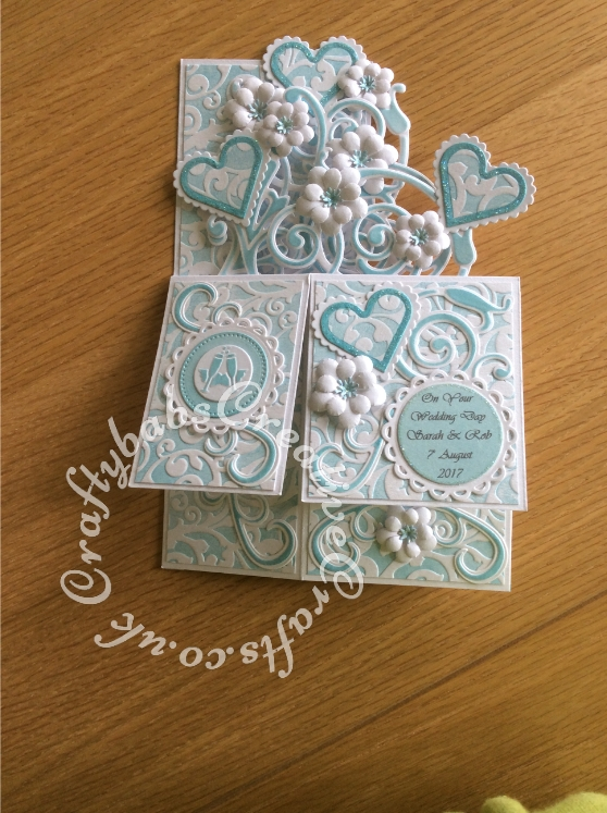 Pop up Wedding card made using a number of dies including; Spellbinders nesting plain and scalloped hearts dies, Cheery lynn flowers dies, Anna griffin flourish scroll die, spellbinders lacey circles dies, Crea Nest lies no 33 dies, leabilities frame square curve die set (for small flourishes). Joy cut & emboss wedding die set, Nellies nesting stitched squares dies, Background embossed with distress ink applied to folder using embossaliscious a4 folder. die cuts inked whilst in die in matching distress ink (Broken China). - craftybabscreativecrafts.co.uk