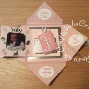 Baby Girl Birth keepsake made using a variety of dies including Quickutz nesting Tag dies, Ellison thick cutz envelope die, Cuttlebug baby elements die, Marianne baby feet dies, Memory Box pram die, nesting plain & scalloped oval dies, Memory box alphabet soup upper and lower case dies, Parchment pocket made using an envelope template stencil, baby clothes and baby words embossed using brass stencils, outer cover embossed using couture creations intrinsic embossing folder - craftybabscreativecrafts.co.uk