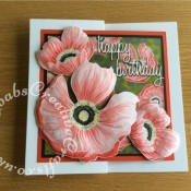 Prima Bloom Floral Stamped birthday card. Background stamped, heat embossed with white pearl embossong powder then masked off with masking fluid. Inked with distress ink and stenciled with mica spray, Masking fluid removed and flowers watercolour painted with Barn Door distress ink. Large flowers heat embossed with white pearl embossing powder and then watercoloured using Barn Door, Mustard seed, Picket fence and black soot distress inks. Flowers then cut out and embossed using various sized ball embossing tools to create dimension. Sentiment die cut using 660223 Sizzix Thinlits Die Set 13PK - Celebration Words Script by Tim Holtz - craftybabscreativecrafts.co.uk