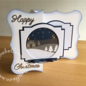 """Large 8"""" x 8"""" Scenic Christmas Card made using a variety of dies including, the free dies from Simply Cards & Papercraft 168, Memory Box country landscape die, Britannia sentiment dies, Nesting circle dies, Memory Box Gross grain ribbon dies and Tonic Studios - Layering Dies - Deco Geometric - craftybabscreativecrafts.co.uk"""