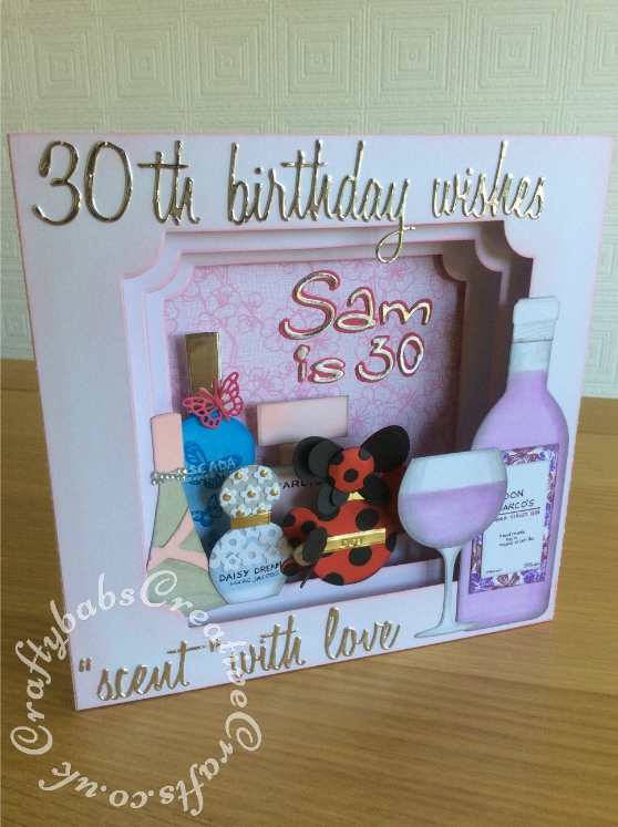 "Large 8""x 8"" Perfume themed Panorama 30th Birthday Card made using Various dies including; Various Sizzix Tim Holtz thinlits 'Script@ words, Sizzix Sizzlits 'Catty Corner' alphabet dies, Numbers from the Sizzix - Tim Holtz - Alterations Collection - Thinlits Die - Alphanumeric, Script alphabet dies, Wine bottle Die from Die Cutting Essentials Magazine Issue 28 and base of glass from same set, top of glass made using Tattered Lace Essentials Teardrop Cutting Dies ETL183 trimmed to shape. Perfume bottles made using various dies including circles, tear drops and trimmed to shape, Base card made using Tattered Lace Large panorama dies partially cut then extended to fit 8""x 8"" card, apertures cut using Tattered Lace Essentials notched Squares dies. - craftybabscreativecrafts.co.uk"