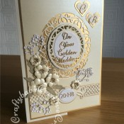 Golden Wedding Anniversary card made using a variety of dies including Tonic Studios Intrica Romantic Vine Die Set ovals, Spellbinders nesting plain & scalloped hearts, Memory box Norrland Flowers dies, Cheery Lynn baby's breath, Britannia alphabet dies, Tattered Lace Wedding Anniversary sentiments, Spellbinders romantic agenda heart and swirls decorative strip dies - craftybabscreativecrafts.co.uk