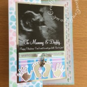 Christmas Card to expectant parents from their unborn baby made using a copy of their actual baby scan in Craftartist professional programme, baby hand and footprints die cut and hot foiled using Recollections dies Baby Hands and Feet Cut and Emboss Dies. Background inked through hearts stencil and insert punch with footprints border punch - craftybabscreativecrafts.co.uk