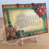 """Christmas Card Plaque made using Mount board, inked with various Tim Holtz Distress and distress oxide inks through Minc Woodgrain Art Screen. Main panel inked with various Tim Holtz distress and distress oxide inks, embossed with Crafters companion Gemini 5"""" x 7"""" 3D Embossing Folder - Merry Christmas and pebeo gilding wax applied. Embellishments die cut using SPELLBINDERS Shapeabilities LAYERED POINSETTIA 7 DIES S5-055, Spellbinders ribbon & bells die set and unknown brand pine needles dies, embellished with Pebeo gilding wax. - craftybabscreativecrafts.co.uk"""