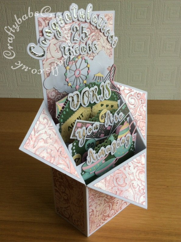 Pop up Box Congratulations card made using various dies including; Nellie's Multi Frames Dies Doily Flower MFD020, Crafters Companion Gemini Expressions Metal Die - Uppercase and lower case Alphabet and number Sets, scenic dies free gift from issue 39 of Die Cutting Essentials magazine, SIZZIX SIZZLITS TEATIME Set 654787, HELZ CUPPLEDITCH DIE - FUN FAIR - TICKET dies, cloud dies from various Xcut build a scene All Aboard die set. Mats and layers on base card embossed with Embossalicious A4 embossing folder, then pearl fininsh addes using Cosmic Shimmer gilding polish accented with Cosmic Shimmer Glitter Kiss. Bingo cards and numbers stamped and embossed using La Pashe flippin bingo stamp set. - craftybabscreativecrafts.co.uk