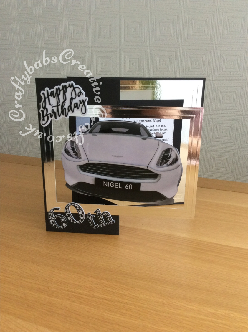 "12"" Square 60th 3D spinning car birthday card made using decopaged images of the car which have been heat embossed with clear embossing powder. Front and rear views mae u[ and then attched together with invisible thread in between to allow supension of completed image within the large aperture in the card allowing it to spin when the card is opened on display. Dies used include; Card Making Magic Die Set Happy Birthday Sentiment and Card Making Magic Die Sets Solid & Overlay Number & Suffix, all multi-cut and stacked to create chipboard like embellishments then heat embossed with clear embossing powder. - craftybabscreativecrafts.co.uk"