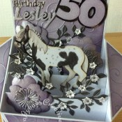 Large Pop up Box Horse themed 50th Birthay card made using various dies including; Quickutz Wildflower die set for large flowers with Cheery Lynn Designs - DIE - Build-a-Flower Embellishments # 3 die for flower stamens, Sue Wilson Finishing Touches Dies - Spring Foilage for branches and small flowers, Quickutz exclusive Remi the Horse revolution die for the horse and saddle, Sizzix Sizzlits Alphabet Script dies for name, Sizzix originals Shadow box numbers dies, Tattered Lace Sentiments 2014 (D211) dies and Paper Boutique Die Set Female Relations Sentiments. Sizzix Sizzlits, Dies Western Set 38-9847 for horse shoes and X cut A4 Embossing Folder. - craftybabscreativecrafts.co.uk