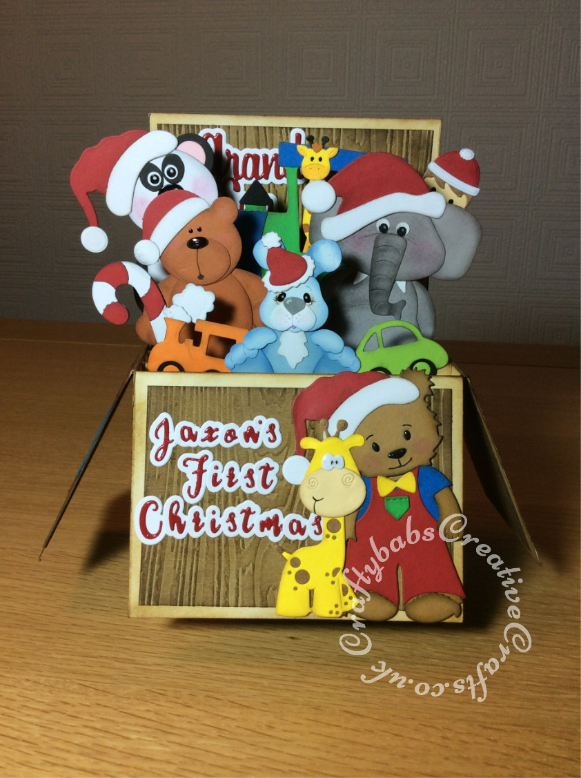 XL sized Toy Box POp Up Baby's First Christmas Card made using various dies including, Toffee bear standing die by Tinker & Co, Jessie bear and outfits dies, Sizzix originals Train, Stocking and Candy cane dies, Spellbinders Die D-Lites Little Guy dies, Bosscut bunnies die, unbranded giraffe dies, Craftycat cistom wooden bear die, Quickutz revolution build an animal dies. Paper boutique sentiment dies and Gemini Expressions Metal Die - Uppercase and lower case Alphabet Sets. - craftybabscreativecrafts.co.uk
