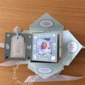 Baby Boy Birth keepsake made using a variety of dies including Marianne Design Cutting and embossing stencils Creatables - My first sneakers, Quickutz nesting Tag dies, Lettering created using Memory box Alphabet soup upper case and lower case alphabet dies, Ellison thick cutz envelope die, Cuttlebug baby elements die, Marianne baby feet dies, Spellbinders nesting plain & scalloped oval dies, Parchment pocket made using an envelope template stencil, baby clothes and baby words embossed using brass stencils, outer cover embossed using Crafter's Companion Basket Weave - Texture 8x8 Embossing Folder. - craftybabscreativecrafts.co.uk