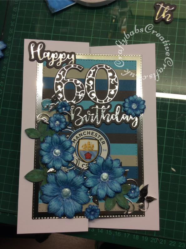 Manchester City themed 60th Birthday Card made using various dies including: Heartfelt Creations Sun Kissed Fleurs die and stamps, John Next Door Leafy Flourish die, iCraft Happy Birthday sentiment dies, Card Making Magic Solid numbers and Overlay numbers dies. Circle die and Sunrise Creations nesting stitched rectangle dies. - craftybabscreativecrafts.co.uk