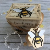 "Bee Happy boxes made using: the Memory Box Small Takeout Box die, the Bee die from The Indigo Blu mixed media Special magazine kit issue one multicut from yellow, black and white card stock, the small bee die and Bee happy stamp from the free cover gift of Issue 163 of Papercraft Essentials magazine . The tag was made using a die from a set of nesting hexagons dies. The glittered patterned paper was from the Docrafts Premium 12"" Bee Happy paper pad. I added stickles glitter and glossy accents to the larger bees. - craftybabscreativecrafts.co.uk"