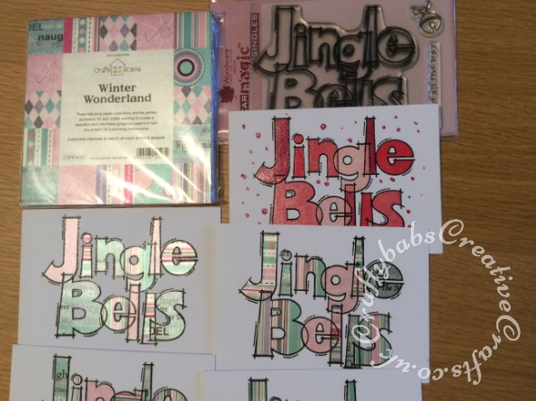 Stamped 'Jingle Bells' A6 landscape Christmas cards made using the Woodware 'HUge Jingle Bells' stamp. Most have been paper-pieced by stamping again onto patterned papers which were then cut out and glued onto the main image. Some were coloured with Spectrum Noir Sparkle pens and some with Spectrum Noir Glitter ink and glossy accents. - craftybabscreativecrafts.co.uk