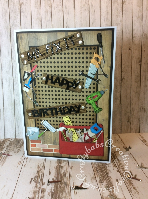 DIY themed birthday card made using various dies including ; Unbranded peg board background die, Toolbox Die, Creative Expressions Craft Dies by Sue Wilson - Necessities - In the Tool Box, Amy Design Die Mans World-Tools Frame, XCUT 24-Piece A5 Die Set, Icons, Marianne Design Craftables Wood Die, Ellison Design / Sizzix Thin Cut Die HARD HAT, All occasion Pipe Works die, Tattered Lace die Happy Birthday (ETL128) and Ellison thin cuts die sign boys zone. Light bulbs stamped onto clear shrink plastic using bulb stamp from the Indigo Blu Mixed Media Special magazine kit, coloured, cut out and then shrunk. Brick pattern on inside achieved using the Hougie score board. - craftybabscreativecrafts.co.uk