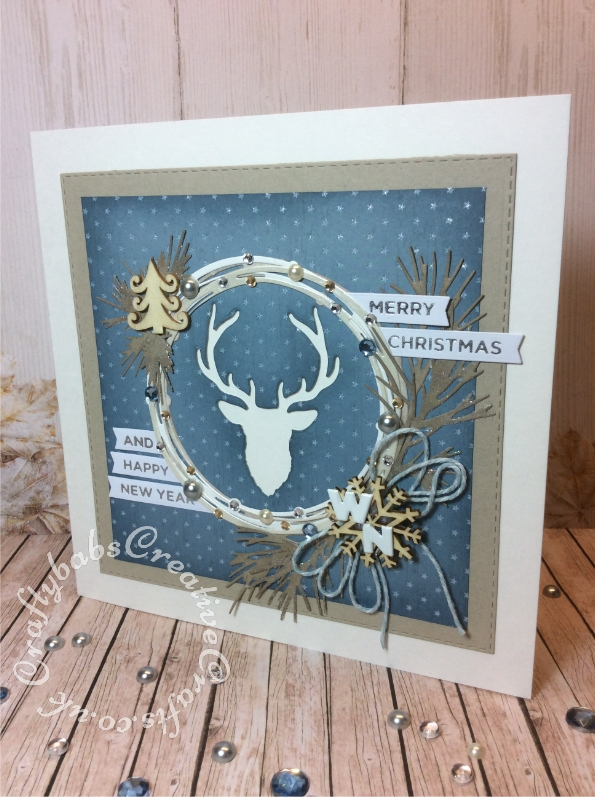 "Contemporary Christmas Card 8"" x 8"" made using various dies including; Sue Wilson Craft Dies - Shadow Box Collection Stitched Square Peg Board for outer mat layer, Spellbinders Hot Foil Plate Christmas Sentiments and small banner dies from JustRite - A2 Card Front Basics Dies set, Wreath circles cut using Tattered Lace Starlights circles die, Deer head cut using die from cover gift of the Simply Cards & Papercraft magazine issue 167. Pine branches cut using Tim Holtz Sizzix Thinlits Holiday Greens Die Set. Embellished with Wooden tree and snowflake embellishments, bakers twine, metal initials brads, Cosmic Shimmer Glitter Kiss and various flat backed pearls and gem stones. - craftybabscreativecrafts.co.uk"