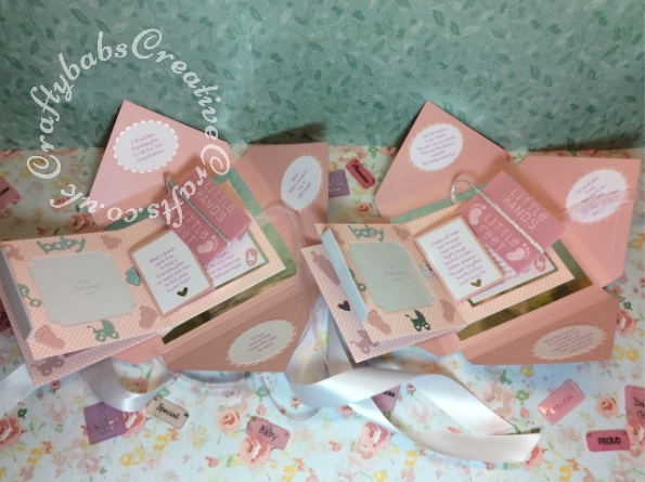 Baby Girl Birth keepsakes, one for the parents and one for the grandparents, made using a variety of dies including: Tattered Lace Essentials Die - Notched Squares ETL311, Quickutz nesting Tag dies, Lettering created using Memory box Alphabet soup upper case and lower case alphabet dies, Ellison thick cutz envelope die, Cuttlebug baby elements die, Marianne baby feet dies, Spellbinders nesting plain & scalloped oval dies, Parchment pocket made using an envelope template stencil, baby clothes and baby words embossed using brass stencils, outer cover embossed using score board. - craftybabscreativecrafts.co.uk