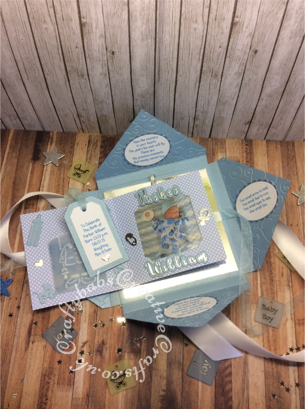 """Baby Boy Birth keepsake made using a variety of dies including Tattered Lace Essentials nesting Notched squares dies, Marianne Design Collectables Cutting Dies - Eline's Babies Col1479, Marianne designs Creatables baby feet dies, MEMORY BOX 98867 """"Baby Bottles"""" die, Memory box Baby clothes die 98625, Quickutz nesting Tag dies, Lettering created using Gemini Die Set Expressions Uppercase Alphabet, Gemini Die Set Expressions Lowercase Alphabet, Ellison thick cutz envelope die, Spellbinders nesting plain & scalloped oval dies, Parchment pocket made using an envelope template stencil, baby clothes and baby words embossed using brass stencils, outer cover embossed using couture creations intrinsic embossing folder. - craftybabscreativecrafts.co.uk"""