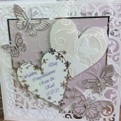 8″ square Wedding card made using included Spellbinders Gold Elements dies, Memory Box Kaleidoscope, moonlight, Pippi, Isabella, Vivienne and Darla butterflies, Bingham and Grand Heart dies. Background embossed with Darice embossing folder then heat embossed over iridescent mica powder. - craftybabscreativecrafts.co.uk